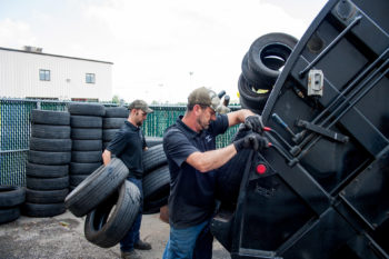 two men loading recycled tires